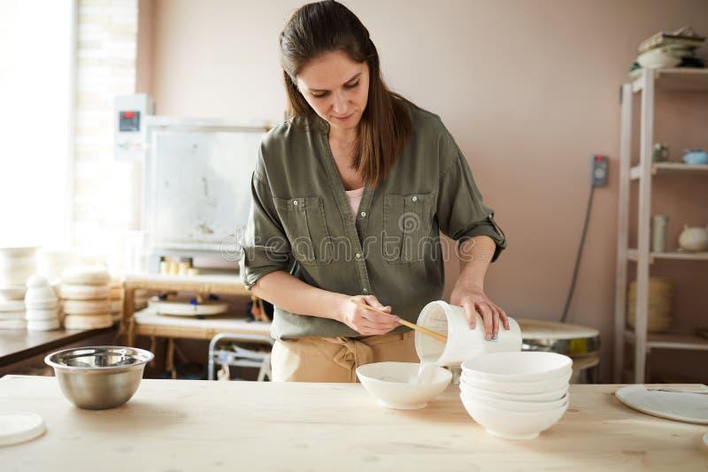 Kvinnligt keramikerarbete shoppar in fotografering för bildbyråer