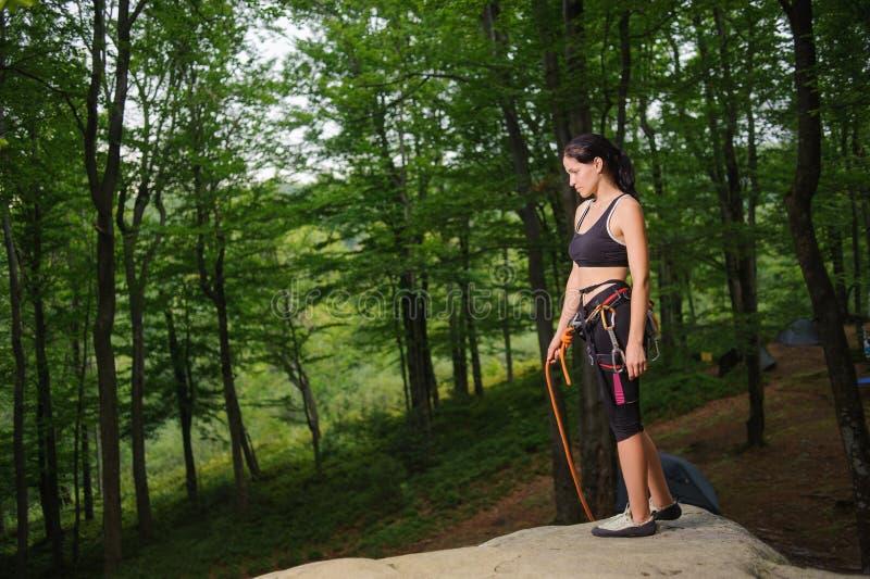 Kvinnligt klättrareanseende på den stora naturliga stenblocket i skogen fotografering för bildbyråer
