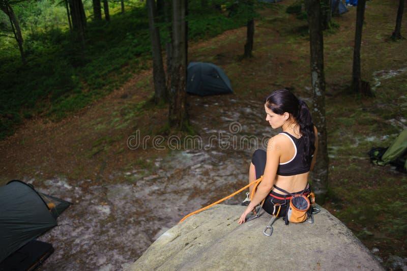 Kvinnligt klättraresammanträde på den stora naturliga stenblocket i skogen royaltyfri bild