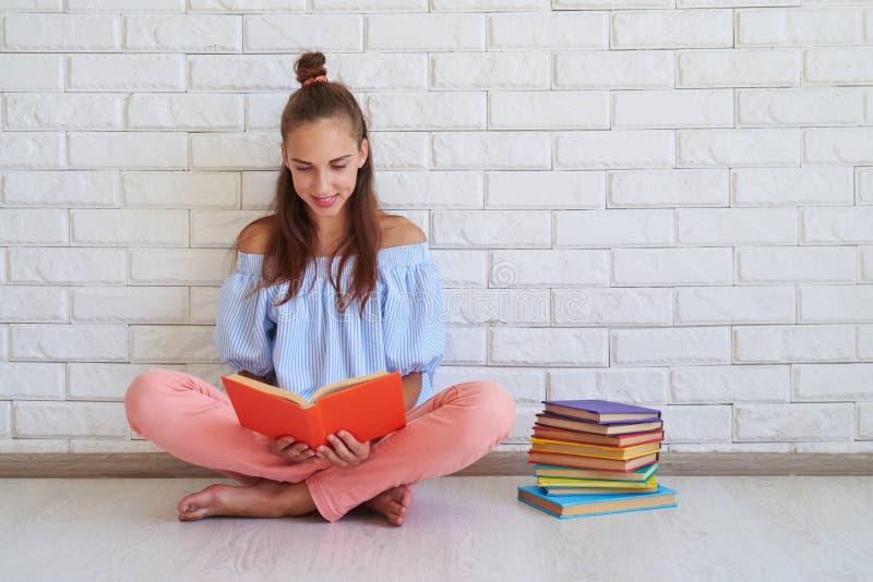 Kvinnligt koppla av för ung brunett på golvet, medan läsa en bok royaltyfri bild