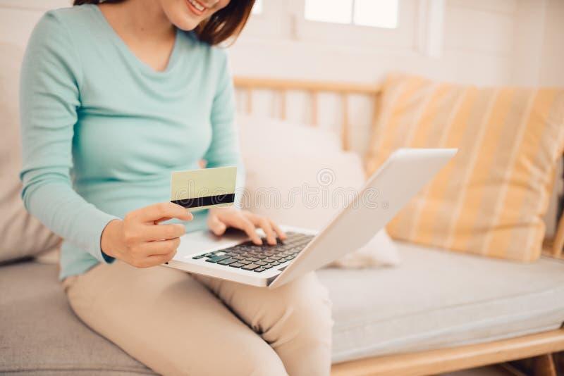 Kvinnligt kundk?pandegods i internetlager, genom att anv?nda kreditkorten f?r online-shopping hemma royaltyfri foto