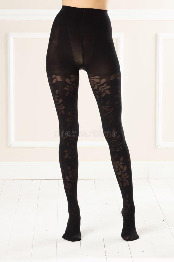 Kvinnligt lägger benen på ryggen i svart strumpor arkivfoto
