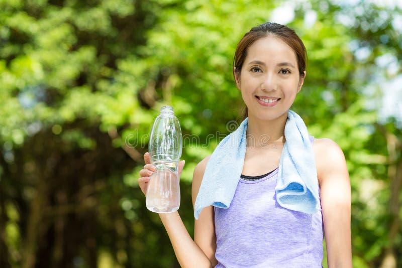 Kvinnligt löparevila och dricksvatten royaltyfri bild