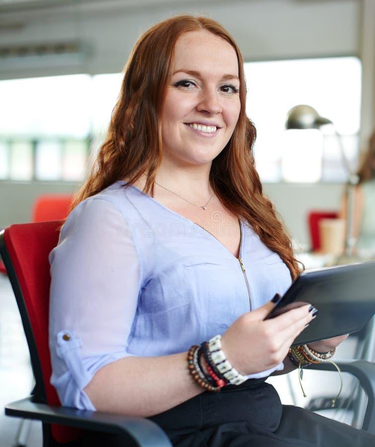 Kvinnligt märkes- arbete för säker rödhårig man på en digital minnestavla i rött idérikt kontorsutrymme royaltyfri fotografi