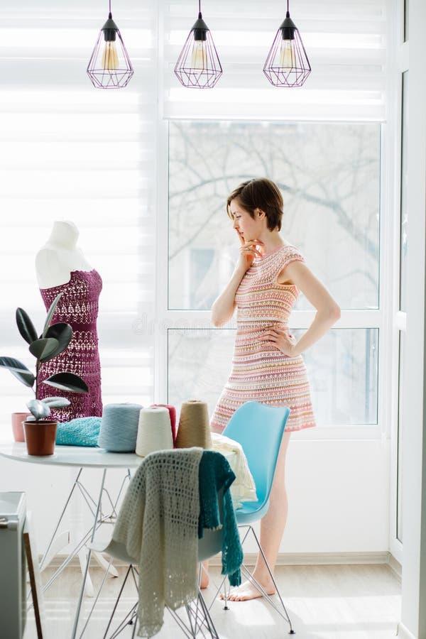 Kvinnligt märkes- tänka, medan arbeta med den stack klänningen i den hemtrevliga studioinre, frilans- livsstil Skjuten lodlinje royaltyfri foto