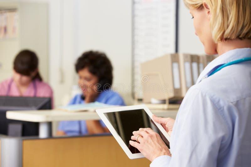 Kvinnligt manipulera genom att använda den Digital tableten på sjuksköterskor posterar arkivbild