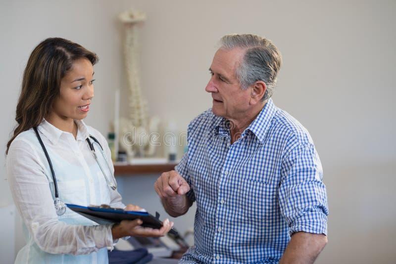 Kvinnligt manligt tålmodigt diskutera för terapeut och för pensionär sparar arkivbild
