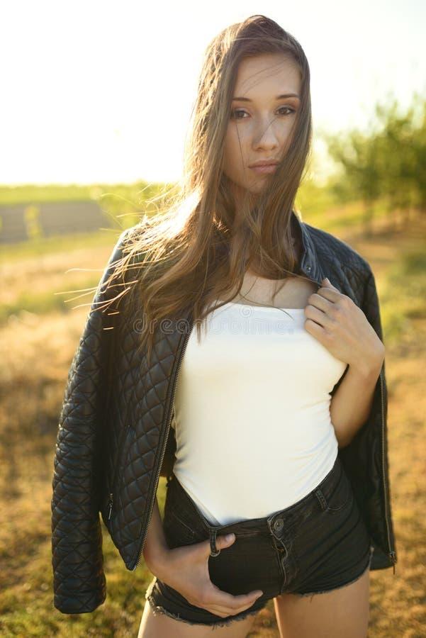 Kvinnligt modellanseende på fältet som tänds av varma solstrålar, hennes hår som blåser i vinden fotografering för bildbyråer