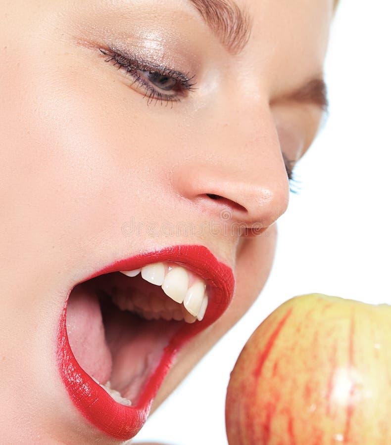 Kvinnligt modellera att bita ett äpple royaltyfri foto