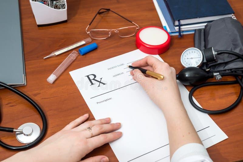 Kvinnligt papper för doktorshandstilrecept med medicinska hjälpmedel fotografering för bildbyråer