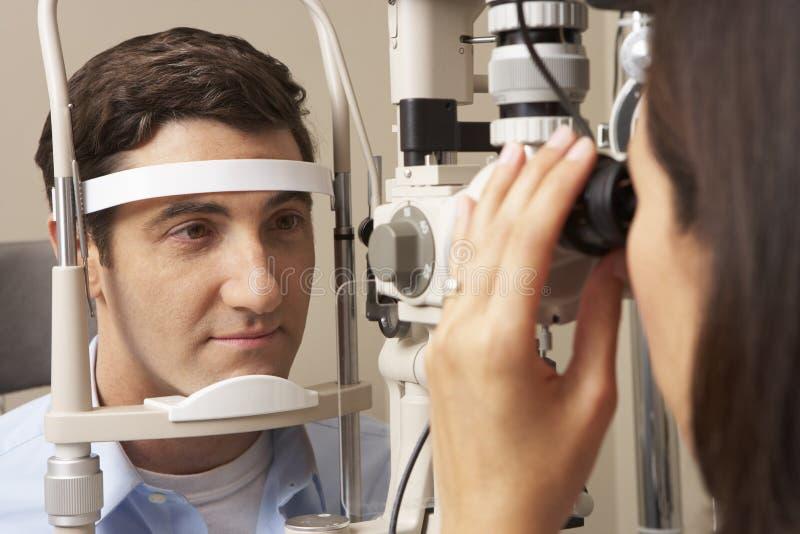 Kvinnligt prov för öga för optikerIn Surgery Giving man arkivbild