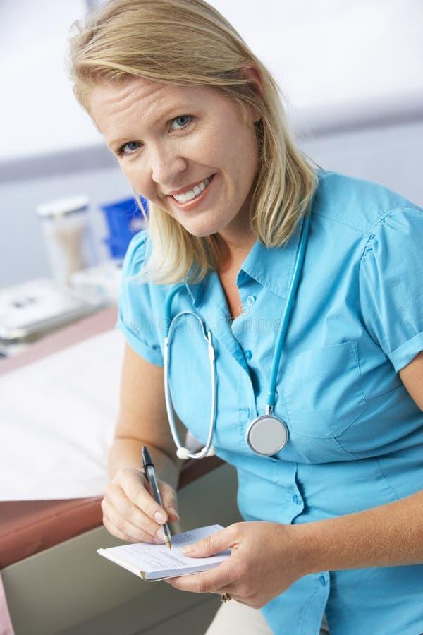 Kvinnligt recept för doktor In Surgery Writing ut arkivfoton