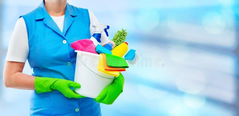 Kvinnligt rengöringsmedel som rymmer en hink med lokalvårdtillförsel arkivbild