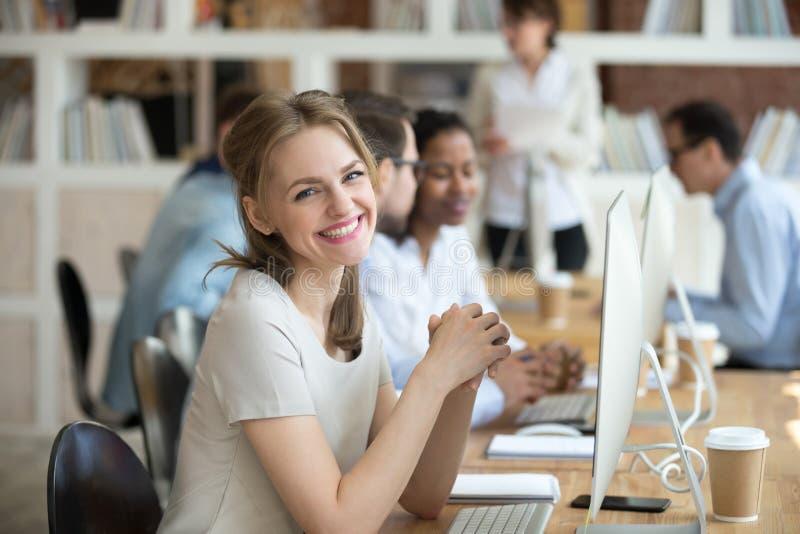 Kvinnligt sammanträde för anställd på skrivbordet mitt emot PC:n som ser kameran royaltyfri fotografi