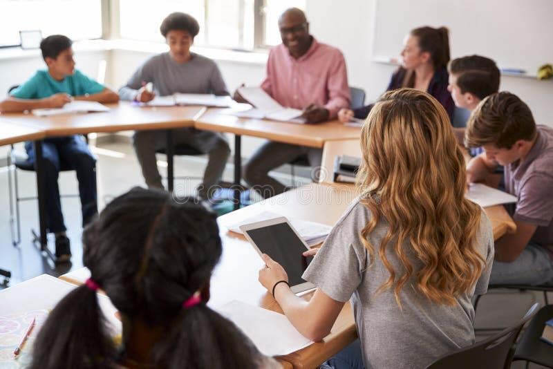 Kvinnligt sammanträde för högstadiumstudentUsing Digital Tablet stund på skrivbordet i grupp arkivbilder