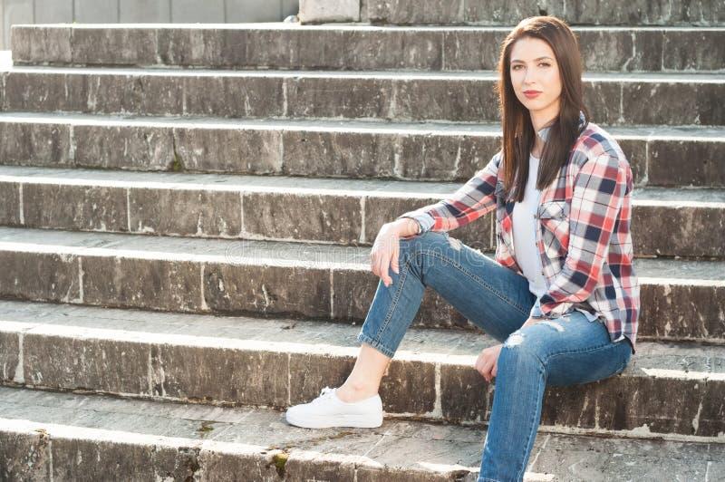 Kvinnligt sammanträde för ung hipster på trappa utanför i tillfällig kläder arkivbild