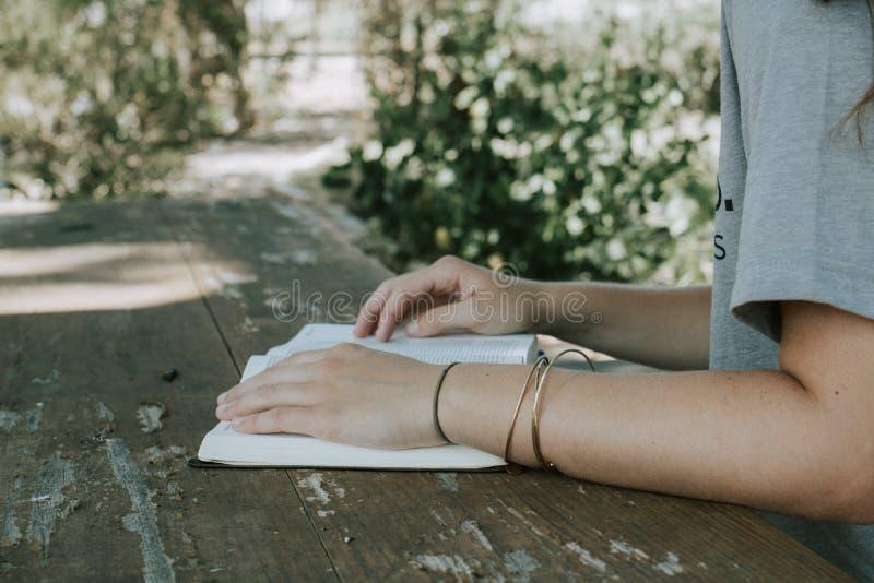 Kvinnligt sitta och läsa en bok i trädgården på en träbänk och en tabell royaltyfri bild