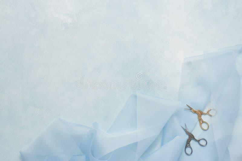Kvinnligt skräddarebegrepp: ljus - blå bakgrund med blått silke arkivbild