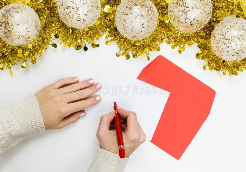 Kvinnligt skriva ett brev till Santa Claus eller ett julhälsningkort arkivfoto