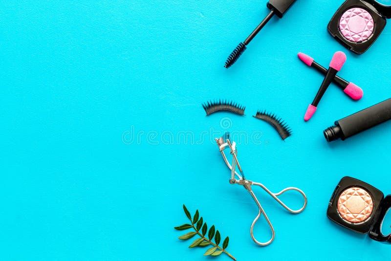 Kvinnligt skrivbord med den dekorativa skönhetsmedlet på flatlay copyspace för blå bakgrund royaltyfria bilder