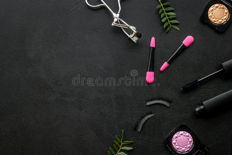 Kvinnligt skrivbord med den dekorativa sk?nhetsmedlet p? flatlay copyspace f?r svart bakgrund arkivbild