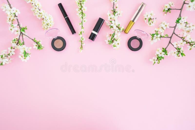 Kvinnligt skrivbord med skönhetsmedlet: läppstift, skuggor, mascara och vitvåren blommar på rosa bakgrund Lekmanna- lägenhet, bäs arkivbild