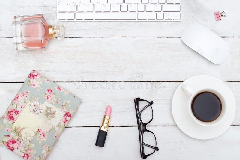 Kvinnligt skrivbord med tillbehör på vit träbakgrund arkivfoton