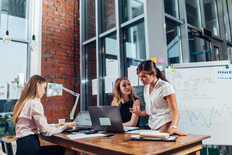 Kvinnligt start-up lag som har en konversation om nytt projektsammanträde på skrivbordet genom att använda datorer i idérik studi arkivfoto