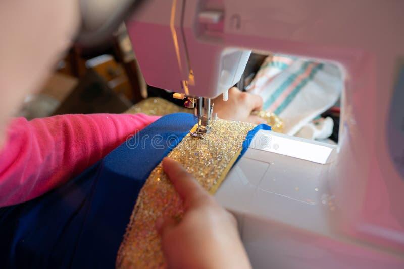 Kvinnligt sy en allhelgonaaftonungedräkt på maskinen arkivfoton