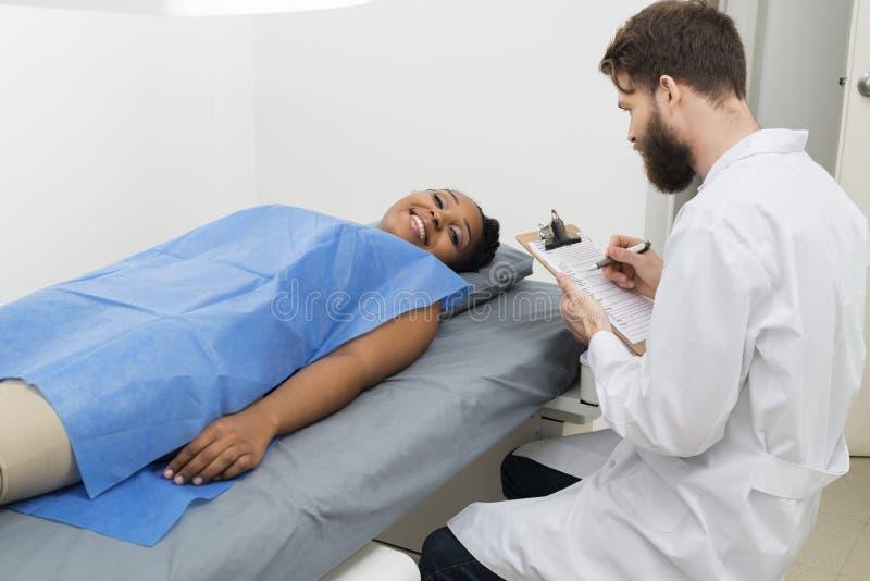 Kvinnligt tålmodigt ligga på säng medan doktor Holding Clipboard fotografering för bildbyråer