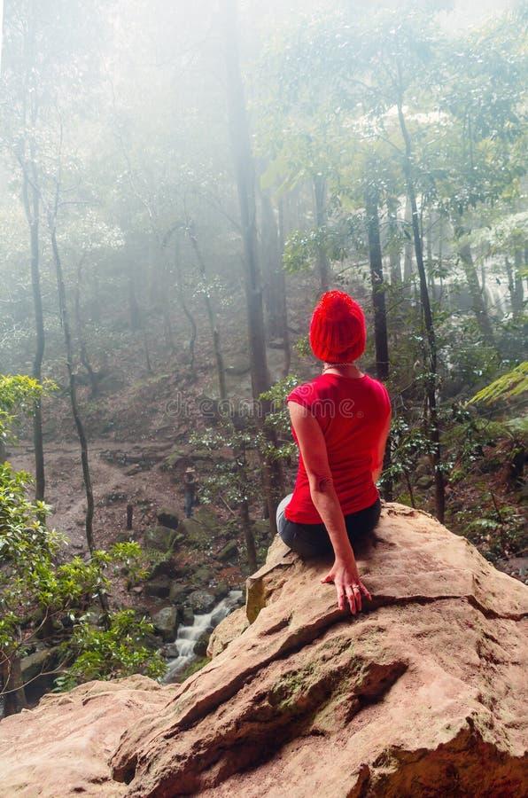 Kvinnligt tagande skydd från regnet i blåa berg för en grottaöverhäng arkivfoto