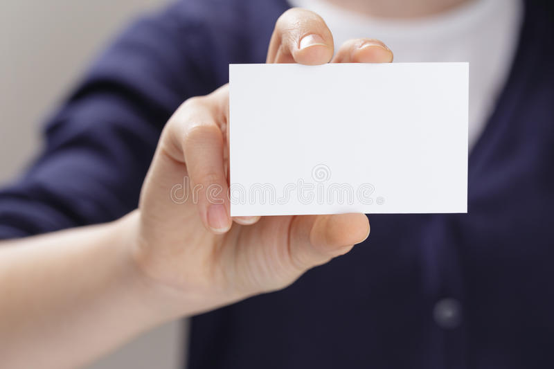 Kvinnligt tonårigt hållande tomt affärskort som är främst av kamera royaltyfri bild