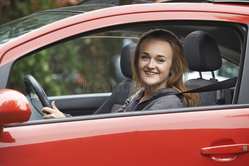 Kvinnligt tonårs- fönster för chaufförLooking Out Of bil arkivfoto