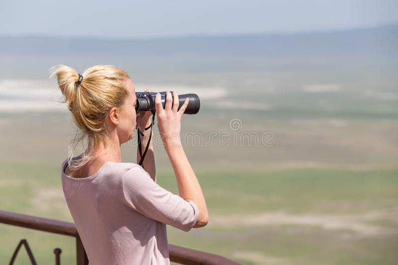 Kvinnligt turist- se till och med kikare på afrikansk safari i område för Ngorongoro kraterconsrvation, Tanzania, Afrika royaltyfri fotografi