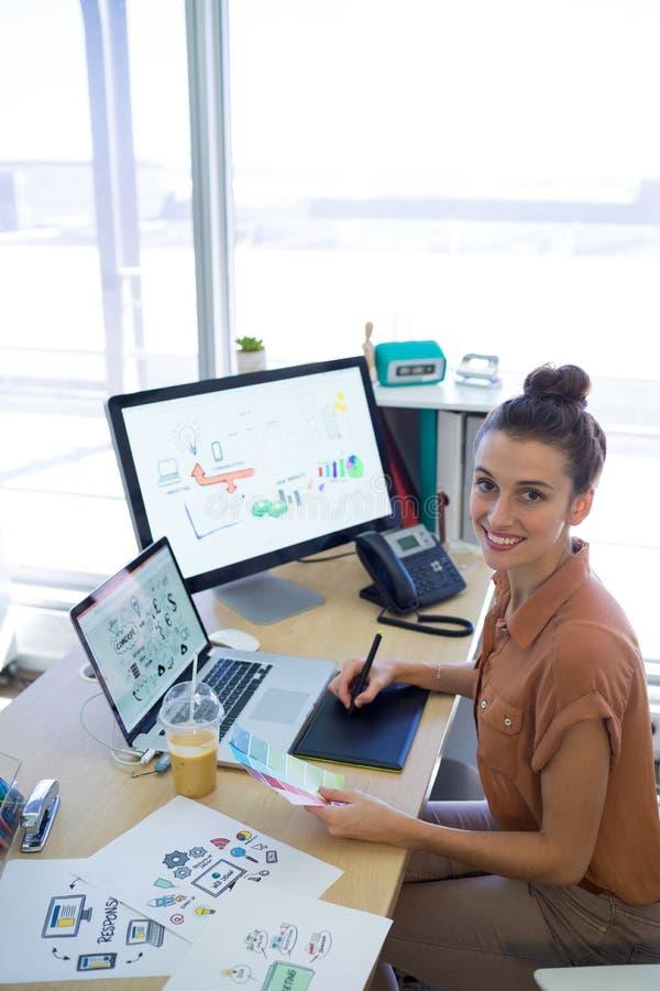 Kvinnligt utövande arbete över den grafiska minnestavlan på hennes skrivbord royaltyfri foto