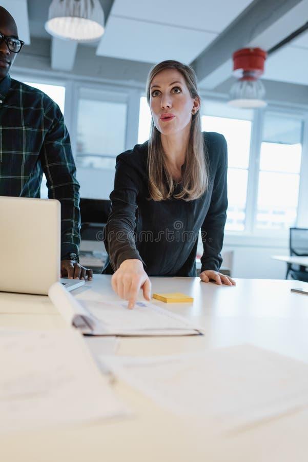 Kvinnligt utövande förklarande affärsplan till hennes lag arkivfoto