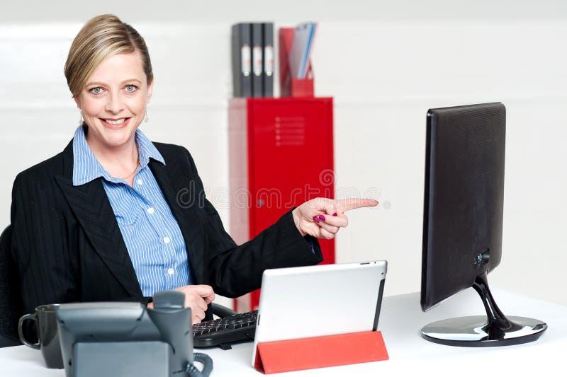Kvinnligt utövande peka på datorskärmen arkivbild