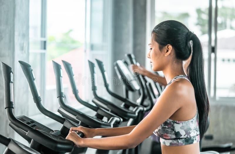Kvinnligt utarbeta på momentklättraremaskinen i konditionidrottshallen för sunt livsstilbegrepp royaltyfri fotografi