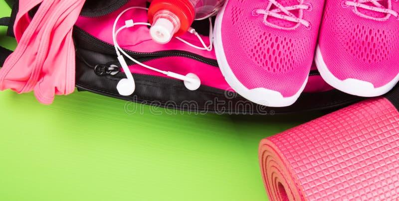 Kvinnliguppsättning av kläder och tillbehör i rosa färger för kondition på en grön bakgrund arkivfoton