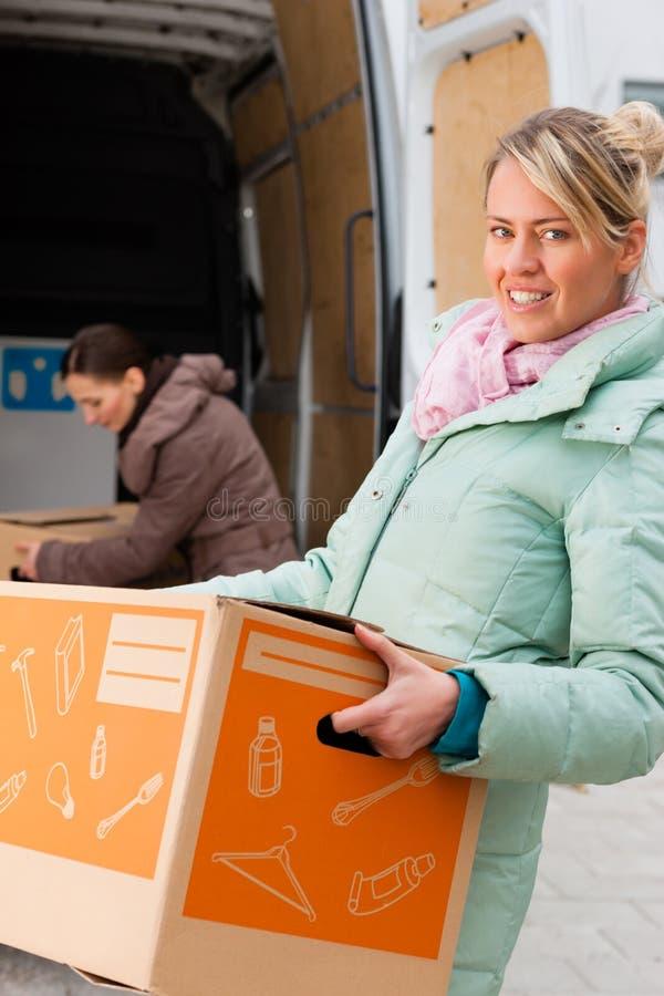 Kvinnligvänner som fyller på en moving lastbil royaltyfria bilder