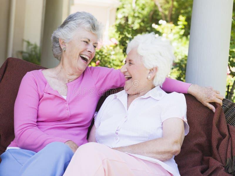 kvinnligvänner som tillsammans skrattar pensionären royaltyfria foton