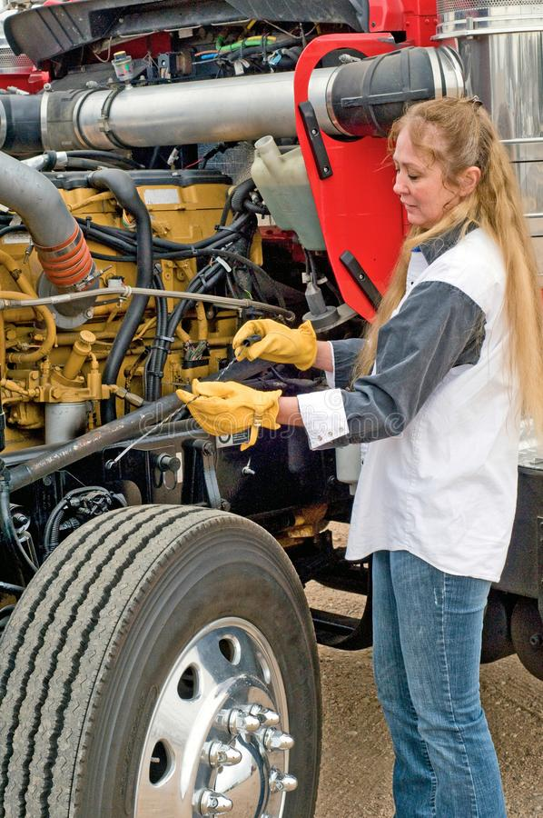Kvinnokontroll av olja under en inspektion före försöket royaltyfria foton