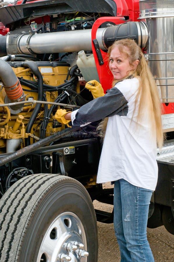 Kvinnolastbilschaufförer som kontrollerar oljenivån på en stor lastbil royaltyfria foton