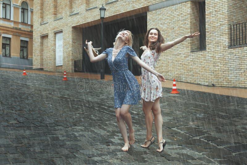 Kvinnor är lyckliga med regnet arkivfoton