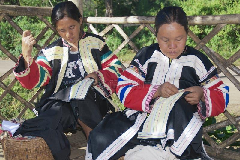 Kvinnor av den svarta Lahu kullestammen gör broderiarbete av de traditionella stam- dräkterna i Mae Hong Son, Thailand arkivbild