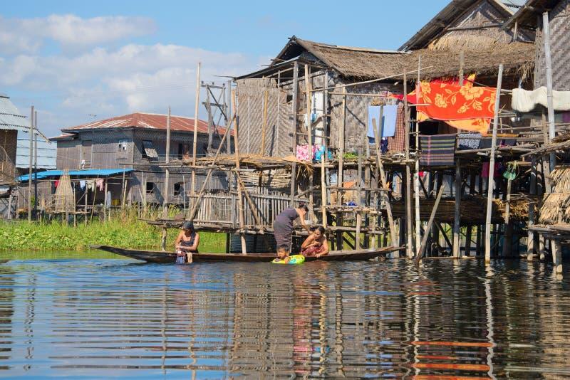 Kvinnor av det Intha folket tvättar sig i sjön nära huset Fiskeläge på Inle sjön, Myanmar arkivfoto