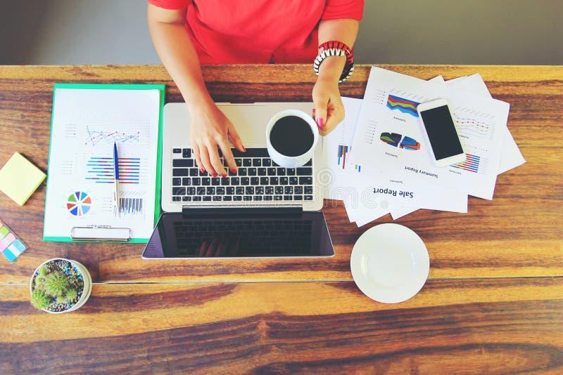 Kvinnor av freelanceren som arbetar genom att använda bärbar datordatoren och handinnehavkoppen kaffe i inrikesdepartementet, kom royaltyfri bild