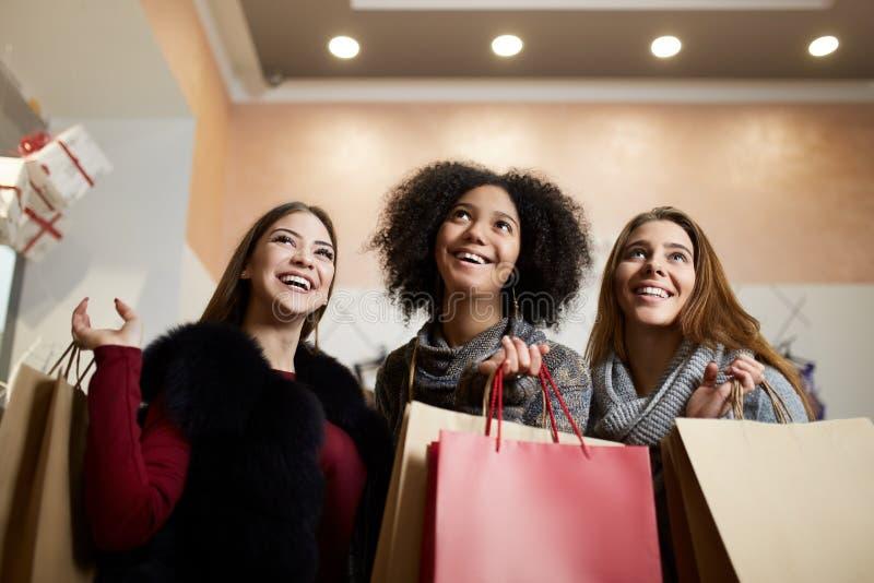 Kvinnor av olik etnicitet med shoppingpåsar som poserar i galleria på försäljning Stående av blicken för tre den le blandras- fli arkivfoto
