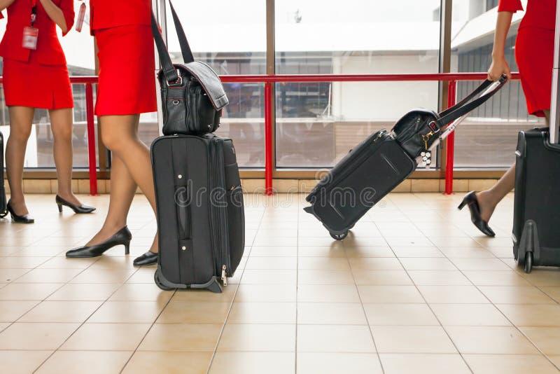 Kvinnor bär deras bagage på flygplatsen royaltyfria foton