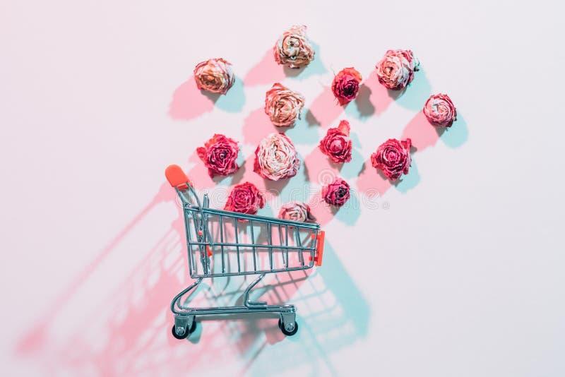 Kvinnor blommar fallande rosor för leveransshoppingvagn arkivfoto